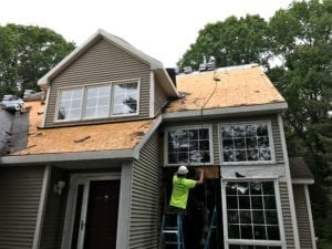 Infinite Roofing crew repairing damaged roofing and siding