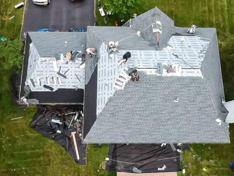 Aerial view of infinite roofing workers on roof