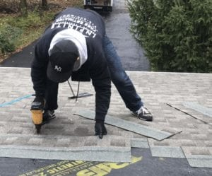 Infinite roofing worker replacing shingles